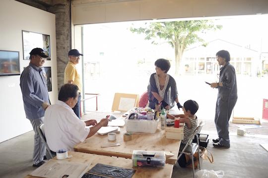 団地内に設置されたオープンスタジオ。右端が上原さん。これまでの作品を紹介するとともに、実際の制作場所ともなり、団地に住む人々と交流も生まれました。(写真提供:伊藤友二)